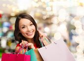 happiness, winter holidays, christmas and people concept - smiling young woman with shopping bags ov