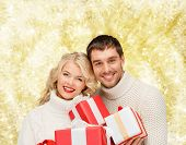 christmas, holidays, happiness and people concept - smiling man and woman with presents over yellow