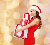 christmas, holidays, celebration and people concept - smiling woman in red dress with gift boxes ove
