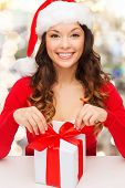 christmas, holidays, celebration and people concept - smiling woman in santa helper hat with gift bo