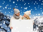 winter, holidays, christmas, advertisement and people concept - smiling couple in winter clothes wit