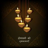 Beautiful illuminated hanging oil lit lamps on floral design decorated brown background with wishes in Hindi text for Diwali festival celebrations.