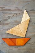 abstract picture of a sailing yacht built from seven tangram wooden pieces over a slate rock backgro