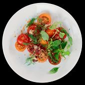 Appetizer with cherry tomatoes and smoked duck fillet isolated on black