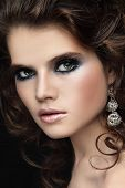 Close-up portrait of young beautiful woman with stylish make-up and curly hair
