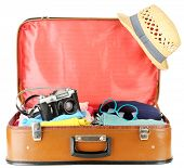 Female clothes and photo camera in old suitcase, isolated on white