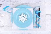 Blue plates, knife, fork, napkin and Christmas decoration on wooden background