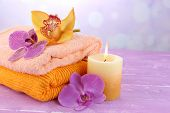Orchid flowers and towels on color wooden table, on light background