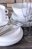 Set of white dishes on table on brick-wall background