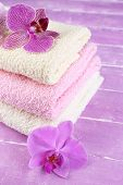 Orchid flowers and towels on color wooden background