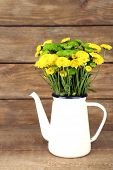 Yellow and green flowers in decorative teapot on color wooden background