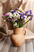 Beautiful bouquet of bright flowers in pitcher on table on brown background