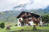 FERRET, SWITZERLAND - AUGUST 30: Beautiful chalet decorated with flowers and with mountains in the background. The village is a stage of the Mont Blanc tour. August 30, 2014 in Ferret.