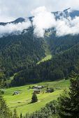 PRAYON, SWITZERLAND - AUGUST 30: Small village at the bottom of forest on hill, with low hanging clo