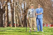 Senior man and a male nurse posing in park on a sunny day