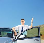 Man holding a car key and standing by an automobile on an open road shot with tilt and shift lens