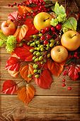 autumn colorful leaves, apples and mushrooms on wooden background