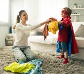 foto of laundry  - Superhero boy and his mother doing laundry together in the living room.