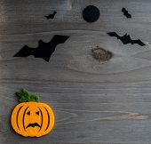 Whimsical Halloween background image of handmade felt jack-o-lantern on rustic wood