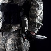 Military man with a knife in a hand close up on the black background
