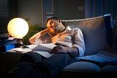 image of nervous breakdown  - Tired businessman sleeping on sofa at home surrounded by paperwork - JPG