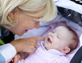 Smiling Grandmother Tickling Baby