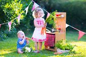 Little Kids Playing With Toy Kitchen In The Garden