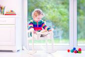 image of daycare  - Cute curly little girl funny toddler wearing a warm colorful knitted dress reading a book relaxing in a white rocking chair next to a big garden view window at home or daycare center