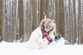 Funny Child Digging In The Snow