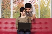 Couple Buy Online At Home In Autumn
