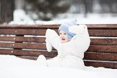 Cute Funny Baby Sitting On A Bench In A Park On A Snowy Winter Day