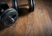 picture of lifting weight  - Black barbell weights on dark hardwood floor weightlifting training concept - JPG