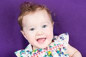 Pretty Baby Girl On A Purple Blanket Wearing A Floral Summer Dress