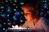 Girl Blows Out The Candles On The Cake