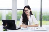 Pretty Woman Smiling At Camera In Office 1