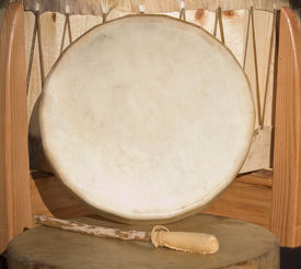 image of buckskin  - Native American Shaman PowWow hand drum and beater leaning against large drum - JPG