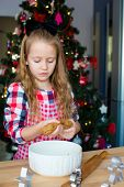 Little girl baking gingerbread cookies for Christmas at home kitchen