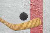 pic of hockey arena  - Puck and stick on the red line hockey rink - JPG