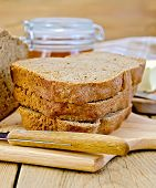 Rye homemade bread with honey and knife on board