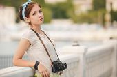 A young woman is engaged in photographing by a digital camera in the city in the summer.