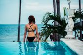 Woman On The Edge Of An Infinity Pool By The Ocean