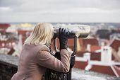 image of binoculars  - Blonde woman takes a looks on the city through binoculars - JPG