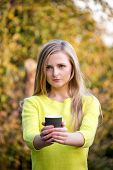 Young beautiful blonde woman offering a cup of take away coffee. Girl having a picnic at the park.