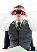 Impressed Businessman Looking Through Binoculars Sitting In His Office