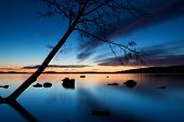 image of bend over  - Silhouette of a tree leaning over Pyhajarvi lake after sunset with blue sky reflecting in water - JPG