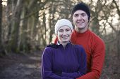 Portrait Of Couple On Winter Run Through Woodland