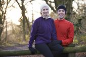 Portrait Of Couple On Winter Run Through Woodland Sitting On Fence