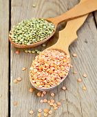 Lentils red and green in spoon on wooden board