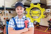 foto of adjustable-spanner  - Confident young male repairman holding adjustable spanner against workshop - JPG
