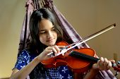 picture of hispanic  - Little Hispanic girl relaxes in a hammock and plays violin - JPG